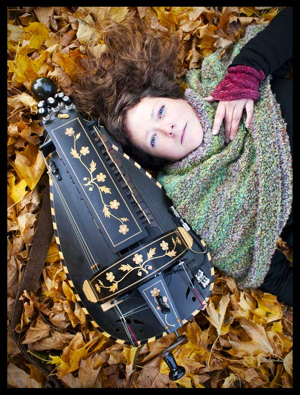 Jess with gurdy in autumn leaves